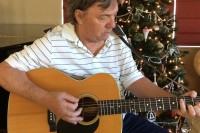 guitarist in front of Christymas tree playing Solitary Angel as Christmas gift