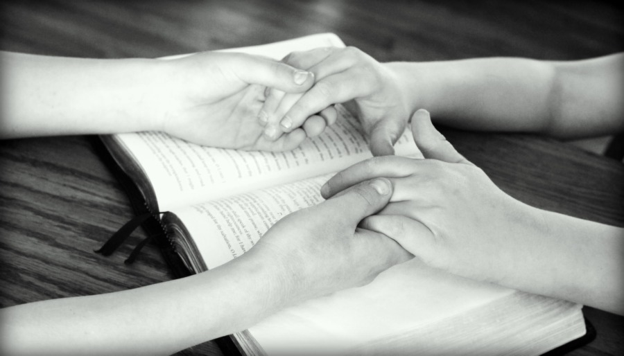 2 people holding hands over scripture