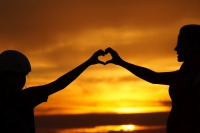 silhouette of 2 people forming heart with extended hands