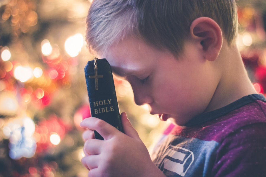 young boy praying with Bible