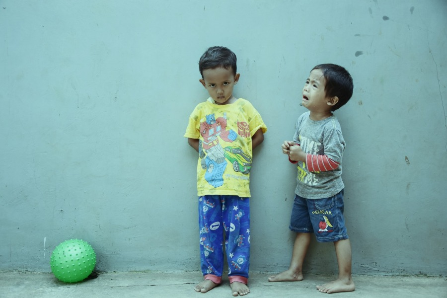 2 small boys, one has caused the 2nd to cry, ball solic background