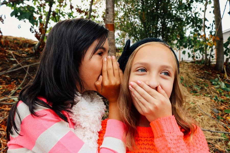 girl whispering into ear of another girl who has covered he mouth