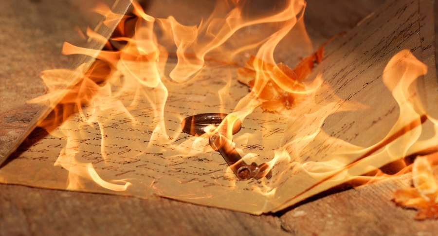 fire imposed on top of key and handwritten pages